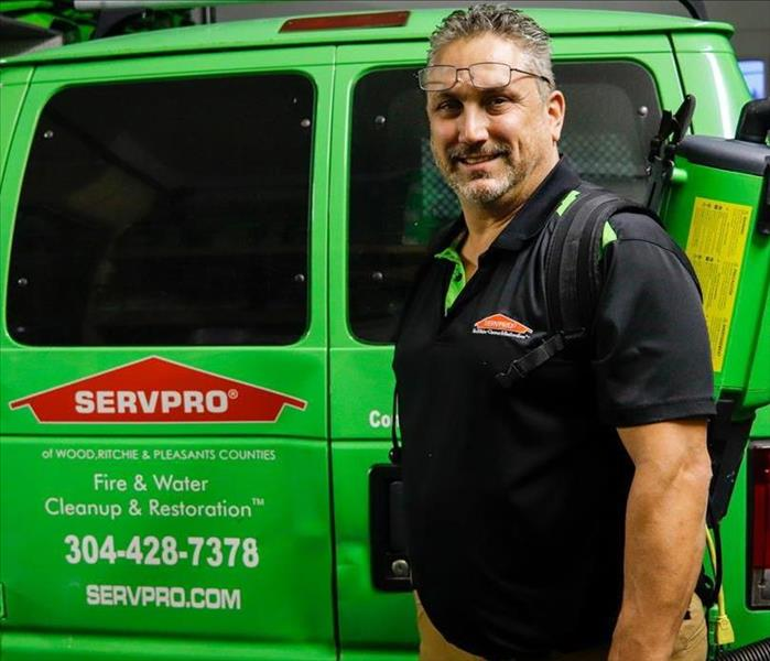 Co-Owner, James Miller, standing and smiling in front of the rear of the SERVPRO van with a vacuum on his back.